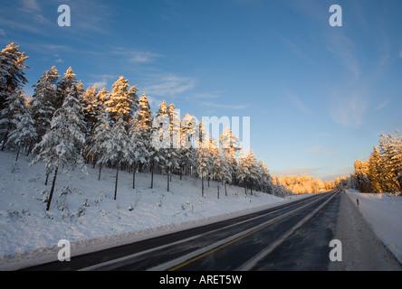 Empty Finnish highway at evening light at Winter Finland - Stock Photo