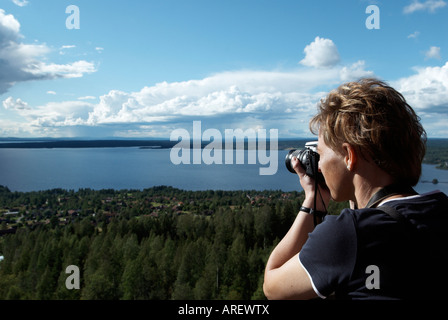 A woman taking a photograph of the Lake Siljan in Vidablick Dalarna Sweden August 2007 - Stock Photo