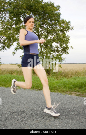 A woman running along a country road - Stock Photo