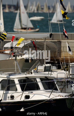 motor boats and cruisers with sailing boats and yachts in the yacht haven marinas at cowes week on the isle of wight - Stock Photo
