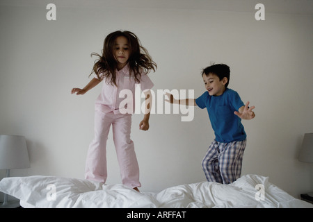 Girl and boy jumping on a bed - Stock Photo