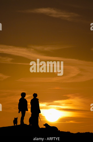 Two walkers with dogs silhouetted against an evening sky on Burbage Edge in Derbyshire 'Great Britain' - Stock Photo