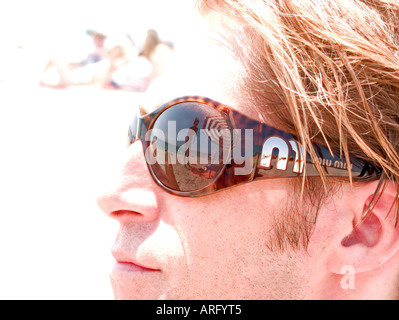 a young man with large contemporary sunglasses looks out to sea - Stock Photo