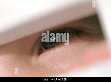 child s eye peeping through letterbox flap - Stock Photo
