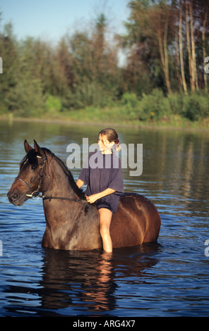 girl and horse cooling down in a pond after riding - Stock Photo