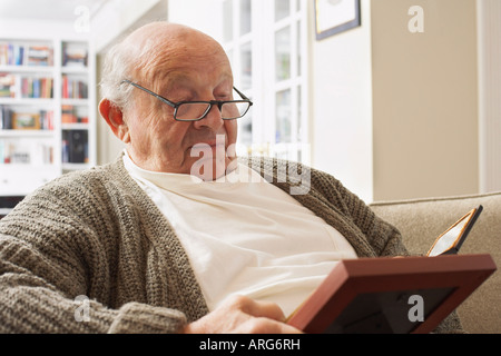 Senior Man Looking at Pictures - Stock Photo