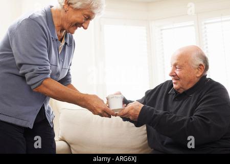 Senior Woman Serving Senior Man Beverage