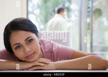 Young woman resting chin on hands - Stock Photo
