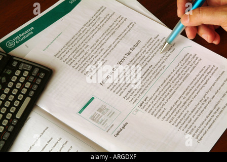 Reading the notes on filling in a Tax Return, UK - Stock Photo