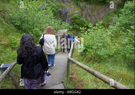 Tourists going down the long steep path to the entrance of the Marble Arch Caves European Geopark show caves national - Stock Photo