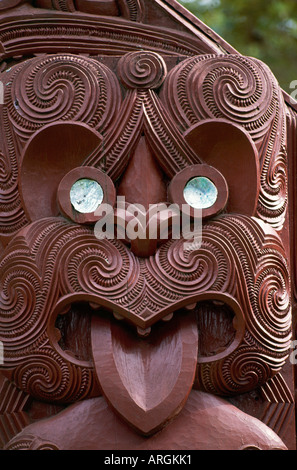 Detail of one of the intricate Maori carvings which represents a major Maori tribe with shining paua shell eyes - Stock Photo