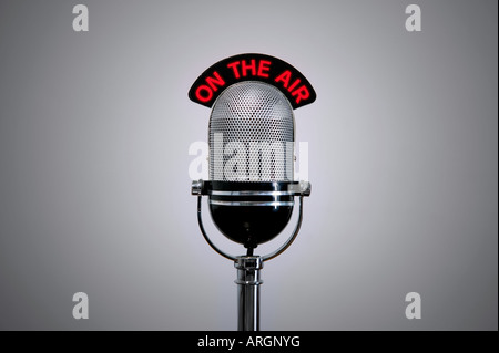 Old retro microphone with illuminated On the Air sign - Stock Photo
