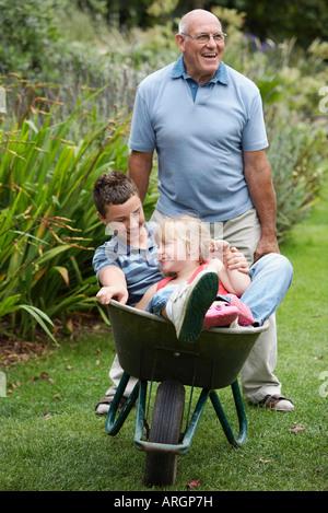 Grandfather Pushing Grandchildren in Wheelbarrow - Stock Photo