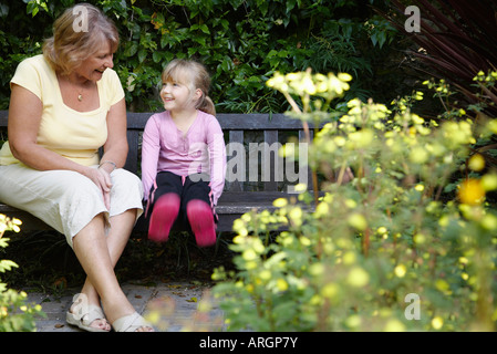 Grandmother and Granddaughter Sitting on Bench in Garden