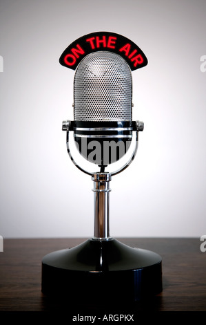 Retro microphone with an On the Air illuminated sign on a desk vignetted background - Stock Photo