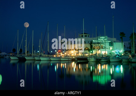 Reflections from a waterfront restaurant highlighting yachts tied up in the large marina at Port El Kantaoui a custom - Stock Photo