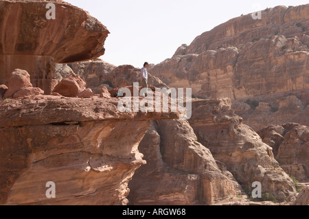 A man standing on the edge of a rock in Petra Jordan - Stock Photo