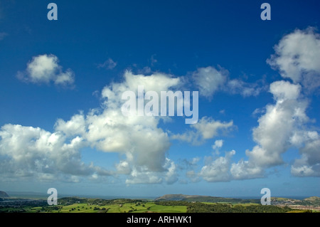 White clouds against a blue sky over countryside - Stock Photo
