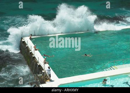A wave breaks over the Bondi Icebergs pool, Sydney, New South Wales, Australia - Stock Photo