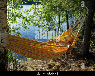 woman lying in a yellow hammock on the lakefront with birches - Stock Photo