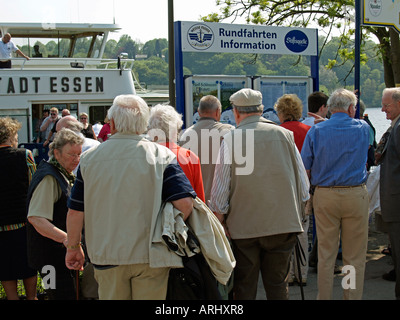 old people group of senior citizens waiting for a pleasure boat at a wharf at the lake Baldeney in the town Essen - Stock Photo