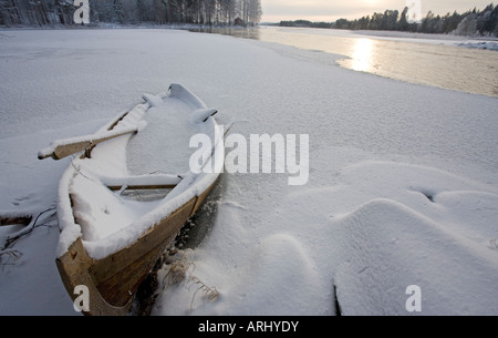 Wooden rowboat frozen into ice at riverbank at Winter , Finland - Stock Photo