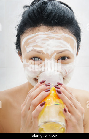 Drinking smiling woman with beauty mask - Stock Photo