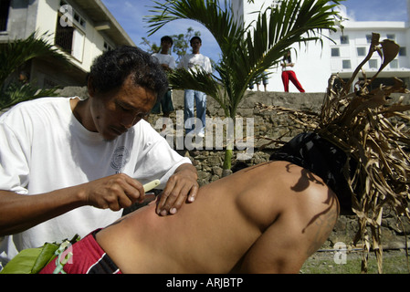 A Filipino cuts the back of a penitent during the annual Good Friday scourging ritual in Mansalay, Oriental Mindoro, - Stock Photo