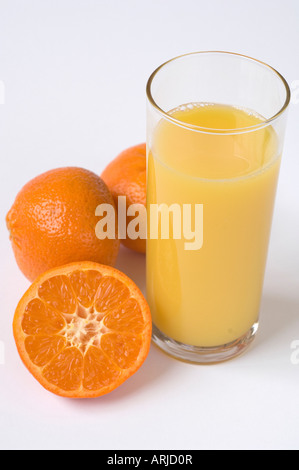 Freshly squeezed organic Orange juice in a glass surounded by sliced & whole oranges against white - Stock Photo