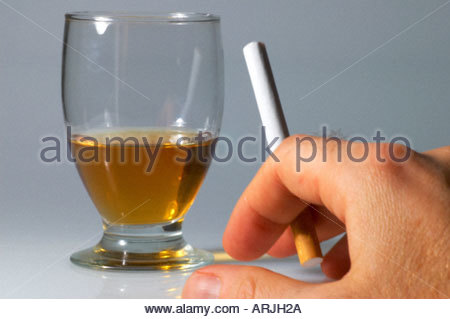 A man smoking a cigarette and reaching for a glass of whisky - Stock Photo