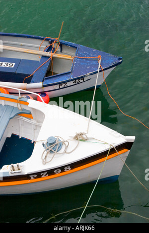 The front end of two moored fishing boats in Mousehole harbour Cornwall UK - Stock Photo