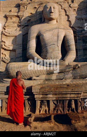 Monk in front of the seated Buddha statue, Gol Vihara, Polonnaruwa, Sri Lanka, Asia - Stock Photo