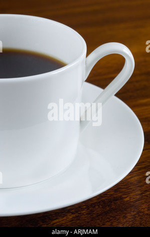 A porcelain cup of freshly brewed and poured Coffee on a white saucer stood on a dark wood table - Stock Photo
