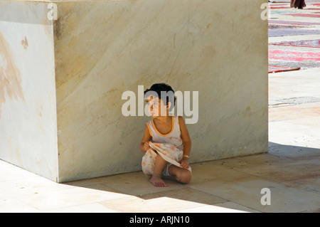 Small girl crouches, waiting,  in the shade, under an arch, courtyard of Umayyad Mosque, Damascus, Syria, Middle - Stock Photo