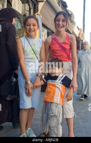 Children pose for photo in the Crowded market of al-Hamidiyya souk, souq, district of Damascus, Syria, Middle East. - Stock Photo