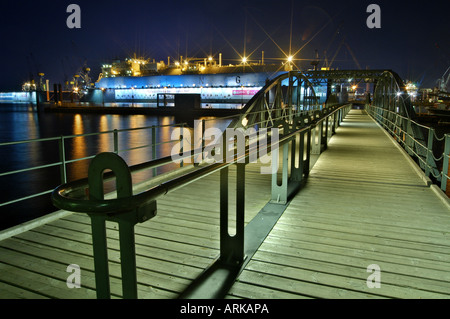 Footbridge to the mooring Fischmarkt Altona in the night In the floating dock of Blohm Voss a cargo ship Hamburg - Stock Photo