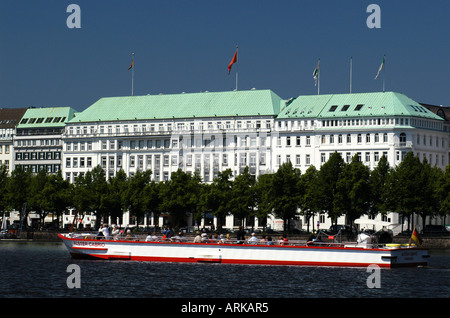 An excursion boat on the lake Binnenalster in front of the luxury hotel 'Raffles Vier Jahreszeiten' Four Seasons - Stock Photo
