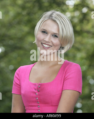 Young blonde woman wearing a tradional Tegernsee dirndl dress smiling into the camera - Stock Photo