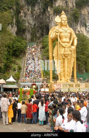 Statue of Hindu deity with pilgrim walking steps up to Batu Caves, Sri Subramaniyar Swami Temple, Batu Caves, Selangor, - Stock Photo