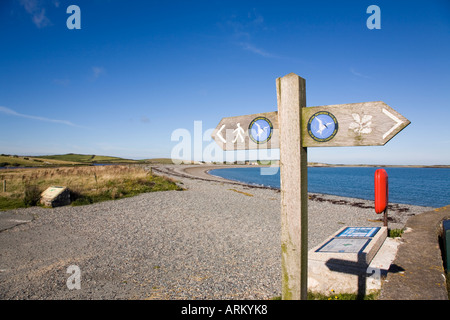 ISLE of ANGLESEY COASTAL PATH SIGN with logo pointing west along shingle beach at Cemlyn Bay Anglesey North Wales - Stock Photo