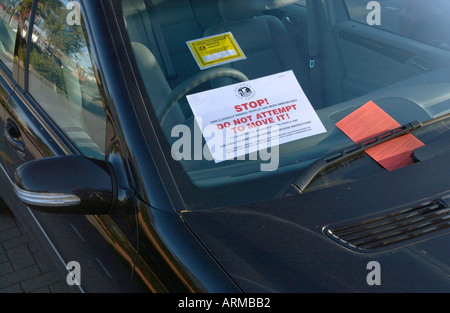 Illegally parked car with parking ticket sticker and penalty notice on windscreen UK - Stock Photo