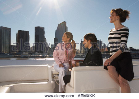 Friends relaxing on boat and looking into distance - Stock Photo