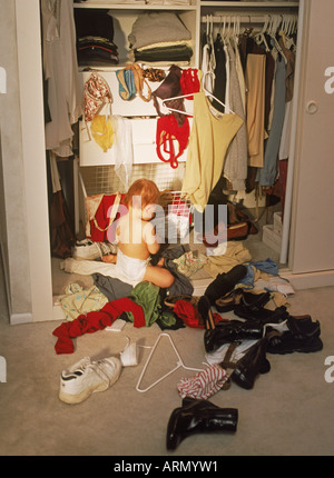 Baby in parent's bedroom closet creating mixed mess of shoes and clothing - Stock Photo