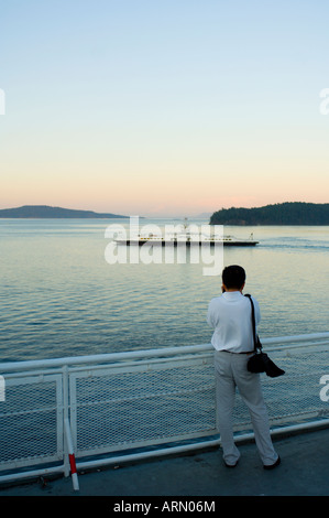 View from deck of BC Ferry, passenger watches smaller Gulf Island Ferry near Sidney, Vancouver Island, Britsh Columbia, - Stock Photo