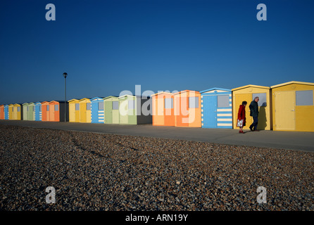 two people walk past a row of brightly coloured beach huts along a shingle beach  at Seaford, Newhaven, Kent, UK. - Stock Photo
