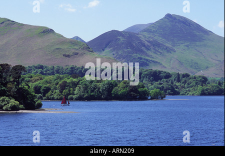 View of Derwentwater with small sailing boat CatBells to left and Causey Pike rise up in the background - Stock Photo