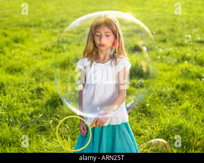 Little girl making soap bubbles - Stock Photo