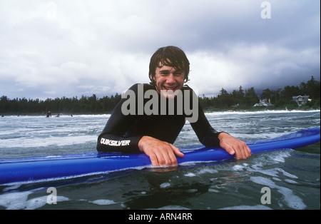 Teenage boy surfing at Long Beach, Pacific Rim National Park, near Tofino, British Columbia, Canada. - Stock Photo
