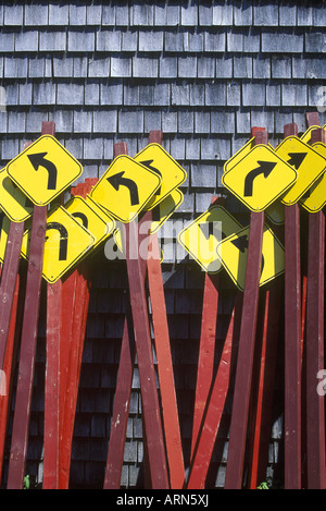Curve ahead roadsigns bunched together against cedar shingled wall, British Columbia, Canada. - Stock Photo