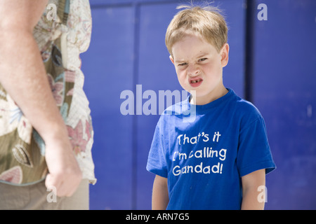 Young boy being scolded and pulling face - Stock Photo